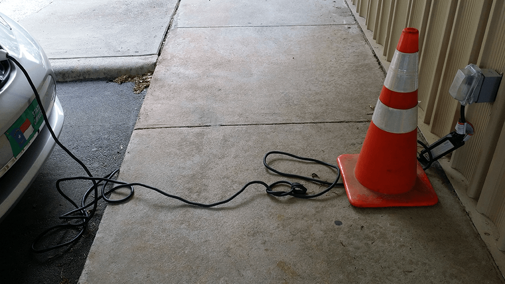 Plugged in charging cord laid messily across sidewalk