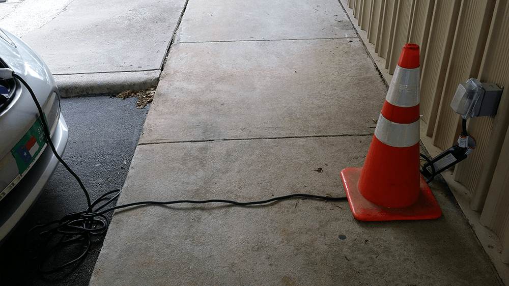 Plugged in charging cord laid straight across sidewalk