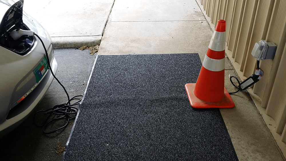 Plugged in charging cord laid straight across sidewalk and covered with rug