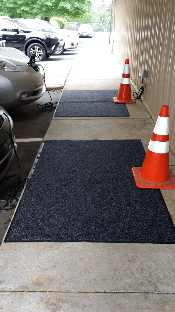 Two electric car charging stations set up with cords coiled and covered with rugs