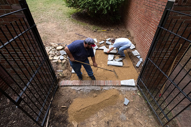 Agustin Delgado (left) and Dwayne Mclaurin create new courtyard paths and decorative areas at Parker Residence Hall.