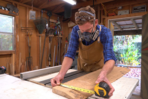 Woodworker Michael Everhart measures a wood plank